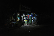 A man smokes a cigarette at a shop in Relocation Golden Valley in Barangay Pagkakaisa outside of Puerto Princesa, Palawan in the Philippines. <br /> Photo: Sanjit Das/Panos for Greenpeace