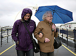Easter Monday bad weather in Southport England. 9.4.12.Two people manage a smile  despite the wind and rain while walking along the pier.