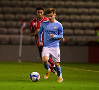Manchester City U21's Ben Knight shields the ball from Lincoln City's Max Melbourne<br /> <br /> Photographer Andrew Vaughan/CameraSport<br /> <br /> EFL Papa John's Trophy - Northern Section - Group E - Lincoln City v Manchester City U21 - Tuesday 17th November 2020 - LNER Stadium - Lincoln<br />  <br /> World Copyright © 2020 CameraSport. All rights reserved. 43 Linden Ave. Countesthorpe. Leicester. England. LE8 5PG - Tel: +44 (0) 116 277 4147 - admin@camerasport.com - www.camerasport.com
