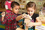 Education Preschool 3-4 year olds girl balancing triangle piece on top of block tower as friend and collaborator looks on