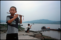 Fengdu, China, August 2003.A little boyl playing his flute .in the old city of Fengdu, already half-destroyed to allow the Three Gorges Dam project to be completed.