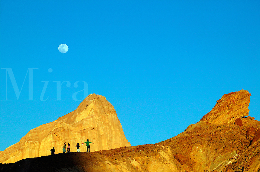 Visitors enjoying the full moon over Manly Beacon from above the Golden Canyon Interpretive Trail, Death Valley National Park, California.