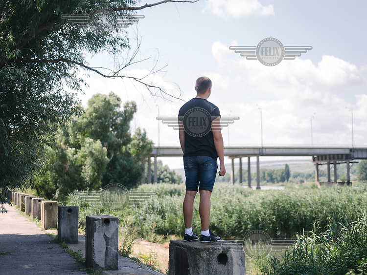 Alexander stands on a bollard and stares towards a bridge that crosses the Dniester River.