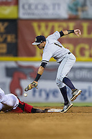 Vicente Conde (4) of the Charleston RiverDogs can't hang on to a pick-off throw as Juremi Profar (23) dives back into second base at L.P. Frans Stadium on August 25, 2015 in Hickory, North Carolina.  The Crawdads defeated the RiverDogs 7-4.  (Brian Westerholt/Four Seam Images)