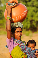 INDIA Chhattisgarh, Bastar, tribal Gond woman with child and clay pot coming from market / INDIEN Chhattisgarh , Bastar, Adivasi Frau des Gond Stammes, indische Ureinwohner, mit Ton Krug