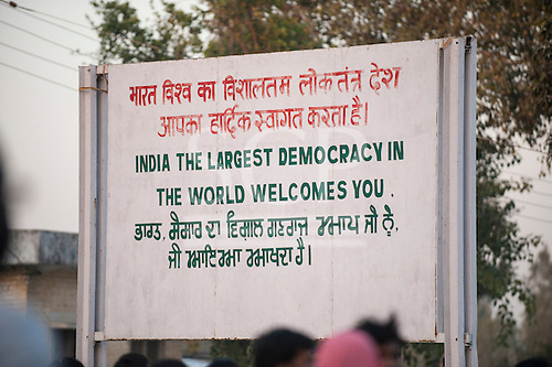 """Amritsar, Punjab, India. Sign: """"India the largest democracy in the World welcomes you"""" at the only land border crossing to Pakistan, written in Hindi, English and Punjabi."""