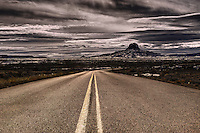 Paved Sandoval County Road 279 east of the village of San Luis in the Rio Puerco Valley, San Juan Basin of northwestern New Mexico with Cabezon Peak in the background.