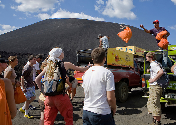 Employees of Bigfoot Hostel throw orange bags stuffed with a protective suits to backpackers awaiting the hike up Cerro Negro volcano, Nicaragua