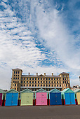 Brighton and Hove, England. Colourful beach huts in front of The King's House council office building.