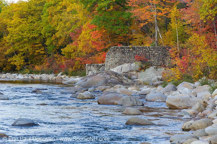 Looking downstream at remnants of the old 1900s Gravity Dam on the East Branch of the Pemigewasset River in Lincoln, New Hampshire during the autumn months. This dam was built during the Lincoln Mill era.