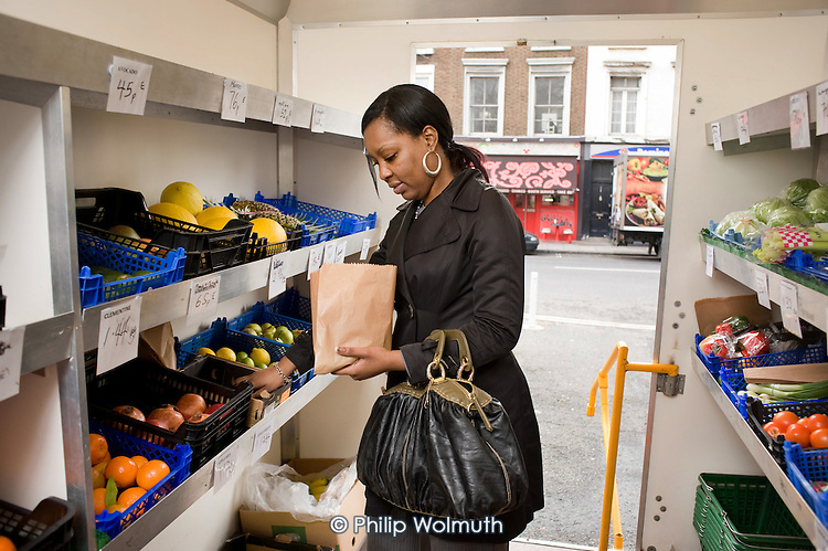 Anita, who works at the Westbourne Park Estate Office, shops at a Mobile Food Unit visiting Brunel Estate, part of a North Paddington healthy eating initiative.
