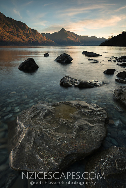 Golden nuggets like rocks on shores of Lake Wakatipu at sunset, Walter Peak in background, Oueenstown, Central Otago, New Zealand, NZ