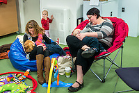 Two mothers breastfeeding at a drop-in breastfeeding support centre.