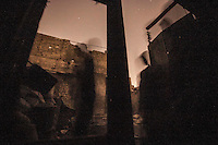 In this Sunday, Nov. 04, 2012 photo, rebel fighters shout muslim hymns as night falls on the Syrian rebel Qastal Al-Harami battlefield in the Jdeide district of Aleppo, the Syrian's largest city. (AP Photo/Narciso Contreras).
