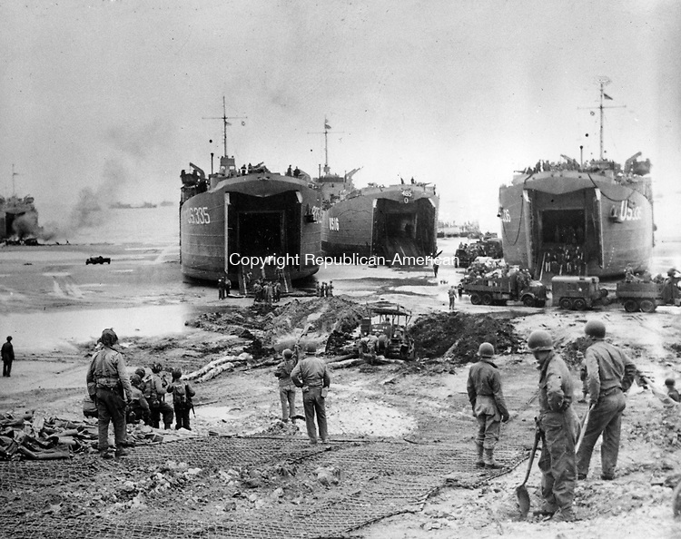 With the combined efforts of U.S. Navy construction battalions and U.S. Army engineers, beachhead roadways fast become realities, providing a steady stream of supplies from LSTs to the fighting troops at the front, during the Allied invasion of Normandy, France, in June 1944. (AP Photo)