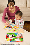 16 month old toddler boy with mother at home playing with puzzle watching as she fits piece into puzzle vertical