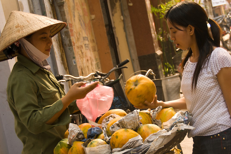 A young woman buys melon in the market of Hanoi, Vietnam.