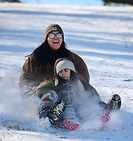Nancy Newton of Prairie Grove laughs Friday, Feb. 19, 2021, as she and her daughter, Abi, 5, ride downhill on a storage container lid while sledding at Battlefield State Park in Prairie Grove. The Newtons were taking a break from virtual instruction to take advantage of the good sledding conditions before warm temperatures melted the snow from the hillside. Visit nwaonline.com/210220Daily/ for today's photo gallery. <br /> (NWA Democrat-Gazette/Andy Shupe)