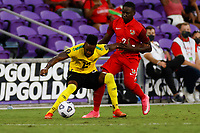 July 16th 2021; Orlando, Florida, USA; Jamaica forward Junior Flemmings holds off Guadeloupe defender Kevin Moeson during the Concacaf Gold Cup match between Guadeloupe and Jamaica on July 16, 2021 at Exploria Stadium in Orlando, Fl.