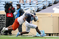 CHAPEL HILL, NC - OCTOBER 10: Michael Carter #8 of North Carolina is tackled by Rayshard Ashby #23 of Virginia Tech at the end of a 27-yard run during a game between Virginia Tech and North Carolina at Kenan Memorial Stadium on October 10, 2020 in Chapel Hill, North Carolina.