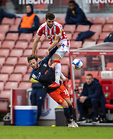 20th February 2021; Bet365 Stadium, Stoke, Staffordshire, England; English Football League Championship Football, Stoke City versus Luton Town; Tommy Smith of Stoke City flattens Tom Lockyer of Luton Town from above and behind