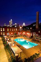 Photography of Charlotte NC's Alpha Mill Apartments, an upscale apartment community near Uptown Charlotte and the NoDa Arts District. Transformed from an historic cotton mill, the Alpha Mill Apartments maintain a part of Charlotte's history. The Alpha Cotton Mill was Charlotte's second cotton mill, according to Alpha Mill Apartment's website. Photo shows the apartments at night with the Charlotte skyline in the background.
