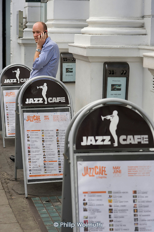 A man uses a mobile phone outside the Jazz Cafe in Camden Town, London.