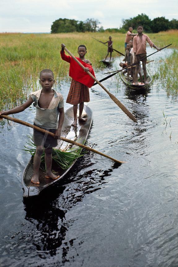 Children of Libinza tribe going to school by canoe, Ngiri river region, Democratic Republic of the Congo (ex-Zaire), Africa.