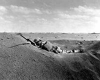 """This Marine, member of the """"Fighting Fourth Marine Division,"""" threatens the enemy even in death.  His bayonet fixed at the Charge, he was killed by intense Japanese sniper fire as he advanced.  February 19, 1945.  Sgt. Bob Cooke.  (Marine Corps)<br /> NARA FILE #:  127-N-109624<br /> WAR & CONFLICT BOOK #:  1223"""