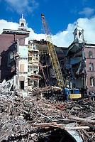 worker standing next to crane during building demolition. worker. CA.