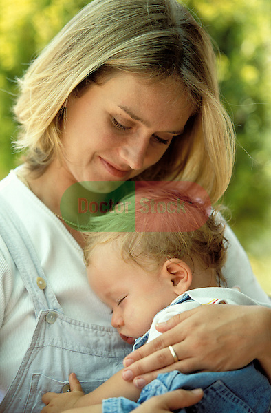 Young mother, 30 years old,  outside in the garden cradling her sleeping one year old son