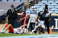 CHAPEL HILL, NC - OCTOBER 10: Dazz Newsome #5 of North Carolina breaks a tackle by Tyler Matheny #30 of Virginia Tech on his 12-yard touchdown reception run during a game between Virginia Tech and North Carolina at Kenan Memorial Stadium on October 10, 2020 in Chapel Hill, North Carolina.