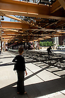 01 JUL 2014 - CHICAGO, USA - A pedestrian waits to cross the road under the tracks of the elevated train system, The L, at the Wells Street and West Wacker Drive junction in Chicago in the USA (PHOTO COPYRIGHT © 2014 NIGEL FARROW, ALL RIGHTS RESERVED)
