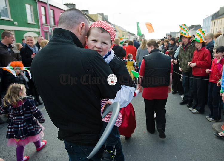 A reluctant Josh Mc Inerney with his dad Josh during the St Patrick's Day parade at Kilrush. Photograph by John Kelly.