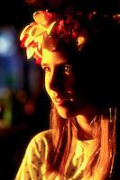 Soft golden afternoon light illuminates the face of a beautiful young girl wearing a haku lei.
