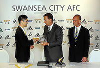 Pictured L-R: Albert Sin of Goldenway exchange gifts with club chairman Huw Jankins and Darren Vickers of Goldenway. <br /> Re: Official launch of the 2013-2014 Swansea City Football Club kit launch, with sponsors Goldenway GWFX at the Liberty Stadium, Swansea, south Wales. Friday 28th of June 2013