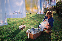 Mother and daughter hanging laundry outdoors.