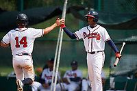GCL Braves right fielder Joel Reyes (25) high fives designated hitter Michael Mateja (14) during the second game of a doubleheader against the GCL Yankees West on July 30, 2018 at Champion Stadium in Kissimmee, Florida.  GCL Braves defeated GCL Yankees West 5-4.  (Mike Janes/Four Seam Images)