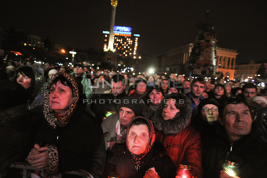 The crowd mourns the victim of Maidan square holding light candles and singing all night long.