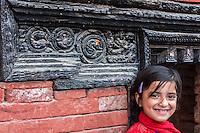 Nepal, Kathmandu.  Hindu Girl at Entrance to Neighborhood Shrine.