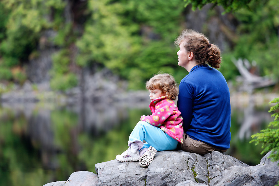 Little girl and mother hikers sitting on rock looking at lake, Boardman Lake, Cascade Mountains, Washington, USA