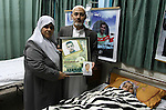 The parents of Palestinian prisoner Fahmi Abu Salah, hold their son picture as they stand next to his wife after she gave birth to a baby boy conceived with Abu Salah's sperm smuggled out of an Israeli prison in Gaza City January 23, 2014.  May, the Gaza wife of a Palestinian prisoner in an Israeli jail, gave birth to her baby boy on Thursday in the second successful smuggling of sperm to lead to a pregnancy in the embattled coastal enclave. Photo by Mohammed Asad