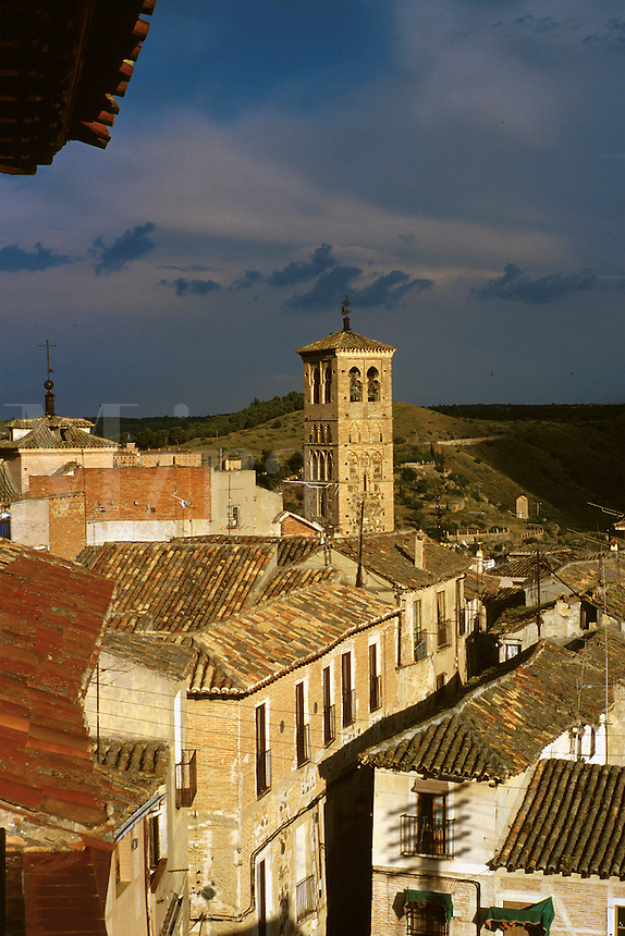 Tower of Church of San Miguel, tile roofs, dark sky. Toledo Castilla-La Mancha Spain.