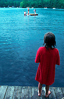 A child stands alone on the dock and watches with longing as other children play in the water of a lake. Vermont.