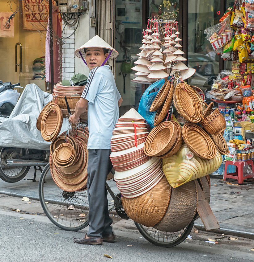 Street vendors ply their trades in Hanoi from bicycles and pushcarts. Here a man sells hats and baskets piled on his bicycle.