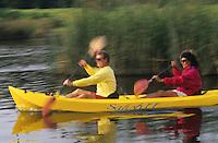 Couple paddling fast in kayak on lake.