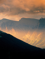 Sun peeking through clouds and shining on mountains of Glacier National Park, Montana.