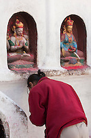 Bodhnath, Nepal.  Worshiper Prays at a Shrine at the Base of the Bodhnath Stupa, a Tibetan Buddhist Stupa.  The Buddha on the left demonstrates the namaskara mudra, a gesture of greeting, prayer, and adoration.  The one on the right makes the bhumisparsa mudra, calling earth to witness, symbolizing enlightenment, steadfastness, impeturbability.