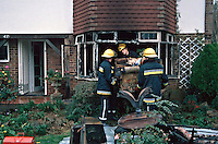 Firefighters removing the contents of a severe lounge fire to the front garden. This image may only be used to portray the subject in a positive manner..©shoutpictures.com..john@shoutpictures.com