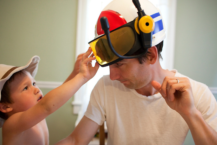 Our older son, age four, outfits his dad with his toy police helmet after breakfast.